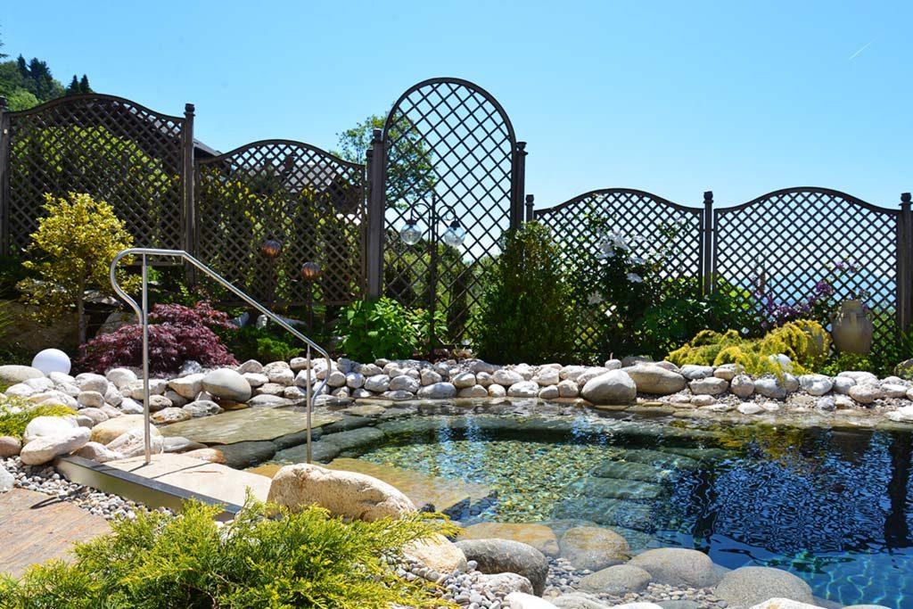 Zum Teich harmonisch passender Gartenzaun